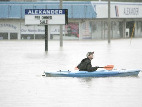 A man paddles his kayak through floodwaters on Fifth Avenue in Franklin on May 2, 2010.