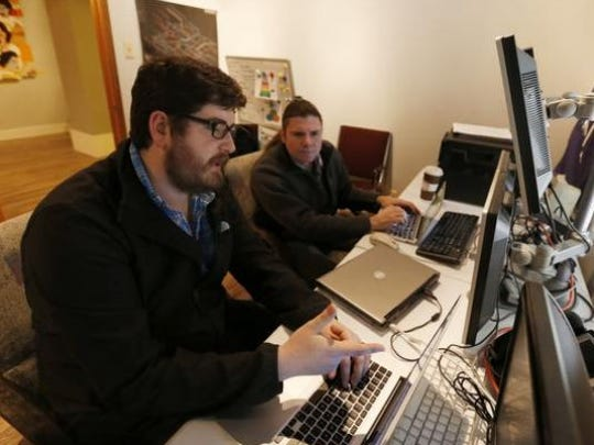 Lead developer Taylor Webber, left, goes over what he's working on with David Miller, CEO of Leverage Holdings in Des Moines.