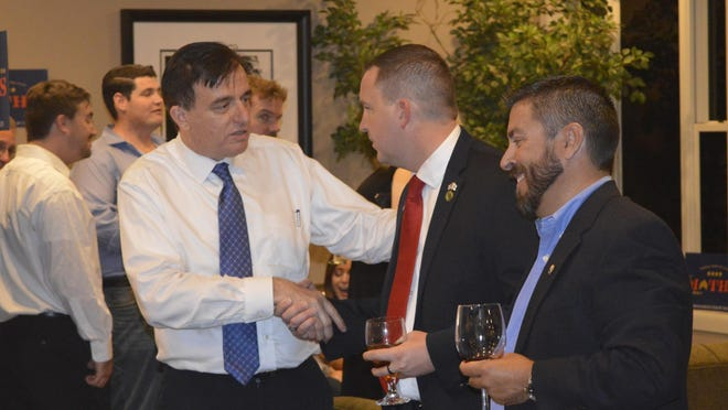 Dr. Benny Benzeevi, left, talks with California Assemblyman Devon Mathis, middle, while waiting for results on Tuesday night.