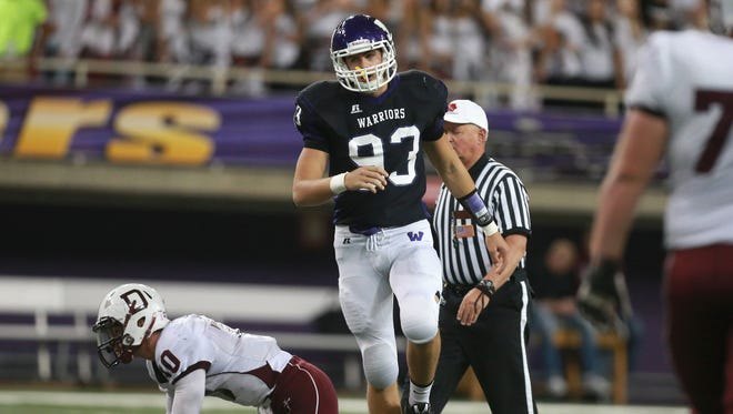 Waukee senior Anthony Nelson towers over Dowling Catholic quarterback Ryan Boyle after sacking him on Friday, Nov. 14, 2014, during the 2014 Iowa high school state football semifinals at the UNI-Dome in Cedar Falls, Iowa.