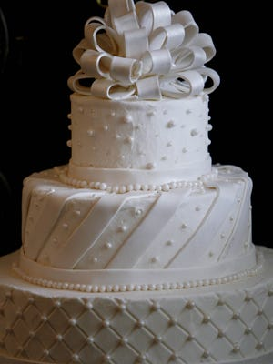 A wedding cake made with fondant and Buttercream with eatable pearls.