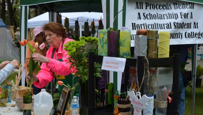 Paula Carmen of Vineland, a member of the Countryside Garden Club, assists with a flower arrangement during the Wheaton Arts Eco Fair. The club sold arrangements in vases, plants and more. Proceeds benefit a scholarship for a horticulture student at Cumberland County College.