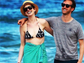 Anne Hathaway and her beau were all smiles while strolling along the beach in this photo.