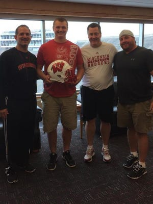 Bay Port offensive lineman Cole Van Lanen (with helmet) poses for a picture at Camp Randall Stadium in Madison after making a verbal commitment to the University of Wisconsin football team. Joining Van Lanen are Wisconsin offensive coordinator Joe Rudolph (left), Wisconsin head coach Paul Chryst (right) and Bay Port football coach Gary Westerman (far right).
