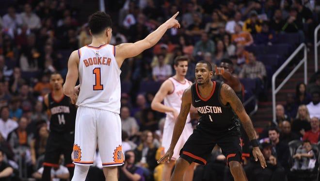 Houston Rockets forward Trevor Ariza (1) guards Phoenix Suns guard Devin Booker (1) during the second half of a game at Talking Stick Resort Arena last season.