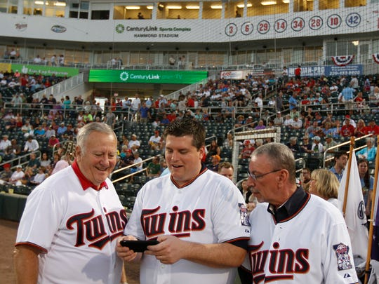 Lee commissioners Frank Mann, Brian Hamman and John Manning view a photo of themselves before the start of the Twins/Red Sox baseball game at Hammond Stadium Thursday in Fort Myers.