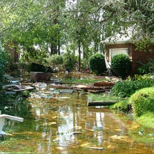 Water drains from the yard of one of Kimberly and Steve Blair's Gulf Breeze neighbors the morning after Hurricane Ivan struck.