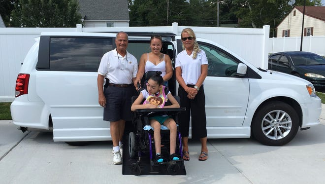 """Zyasia """"Lovey"""" Guzman, 11, of Vineland (front) is pictured in front of her new handicapped-accessible van along with (from left) Bart Brigidi, organizer of the effort to raise funds to provide Lovey with a van; Christina Guzman, Lovey's mother; and Caroline O'Brian of Mobility Works Corp."""