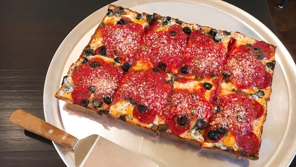 A Detroit-style pizza with crispy, chewy cheese baked