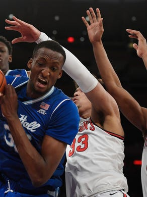 Seton Hall center Romaro Gill (35) catches a rebound against St. John's forward Ian Steere (33) and guard Mustapha Heron (0) during the first half of an NCAA college basketball game in New York, Saturday, Jan. 18, 2020. (AP Photo/Sarah Stier)