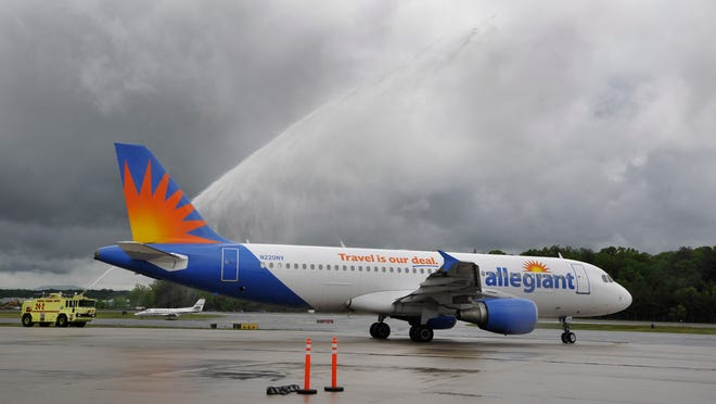 Allegiant Airlines flight 820 departs Asheville Regional Airport on its inaugural flight to West Palm Beach through a water cannon spray by the airport fire department.