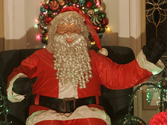 A blow-up Santa waves to passing motorista as part of the Parze family holiday display at their Freehold Township home.