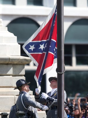 An honor guard from the South Carolina Highway patrol removes the Confederate battle flag from the Capitol grounds in Columbia, S.C., ending its 54-year presence there.