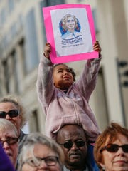 Sydney Smith, 4, holds up a sign while sitting on father