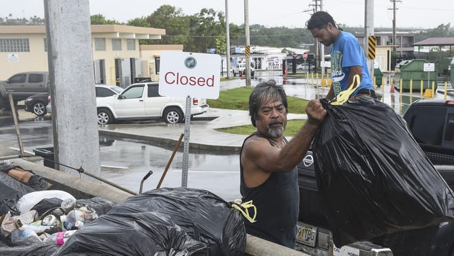 Micky Cornelio, right, and Steve Danis throw household trash into a receptacle at the Guam Solid Waste Authority Transfer Station in Upper Tumon in Sept. 3, 2015.