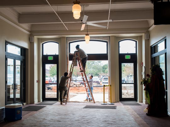 Workers put the finishing touches in the breezeway at One Palafox Place in downtown Pensacola on Thursday, November 30, 2017.