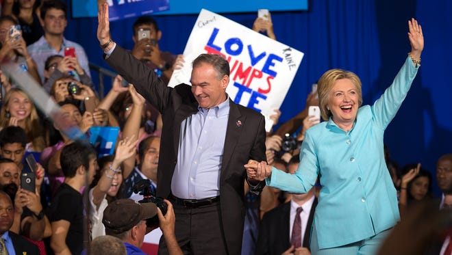 Secretary of State Hillary Clinton walks on stage with her vice presidential running mate, Sen. Tim Kaine, D-Va., at a campaign rally at Florida International University in Miami on Saturday, July, 23, 2016. The rally was the first public appearance of Kaine after being named Clinton's running mate.