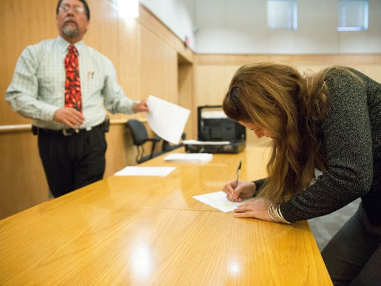 Gema Morales registers for the Doña Ana County Property Tax Auction, Friday Dec. 15, 2017 at the Doña Ana County Government Center. During the auction the Doña Ana County Historical Society bid and won the auction for the Old Picacho Cemetery.