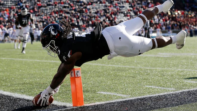 Cincinnati Bearcats running back Mike Boone (5) leaps and stretches to put the ball across the goal line for a game-tying 2-point conversion in the fourth quarter of the NCAA football game between the Cincinnati Bearcats and the Connecticut Huskies at Nippert Stadium in Cincinnati on Saturday, Nov. 25, 2017. The Bearcats took a 22-21 win on senior day after the Huskies missed an extra point attempt with no time left on the clock.