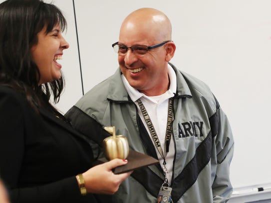 Mariner High School JROTC teacher Esteban Jaramillo reacts to winning the Golden Apple on Friday.
