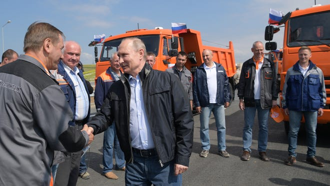 Russian President Vladimir Putin meets with workers during an opening ceremony of the road section of the Krymsky (Crimean) Bridge over the Kerch Strait, Crimea, on May 15, 2018.