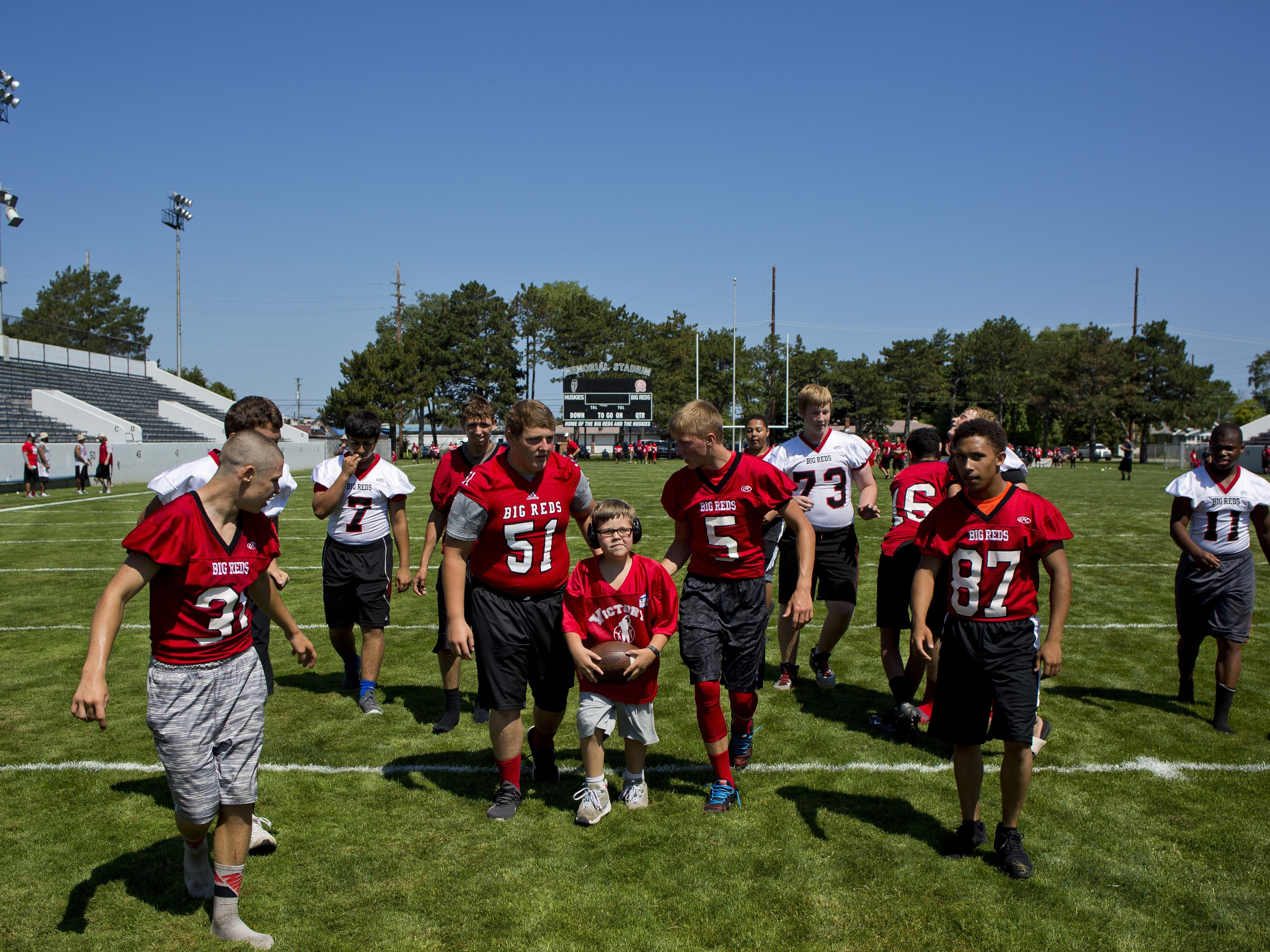 Johnathan Larson, center, is cheered on as he runs the ball down field during Victory Day Saturday, August 15, 2015 in Memorial Stadium at Port Huron High School. The event paired special needs students with mentors from the football and cheerleading teams.