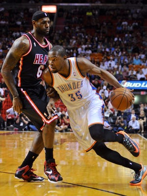Thunder small forward Kevin Durant (35) drives to the basket as Heat small forward LeBron James (6) defends during Oklahoma City's win Wednesday.