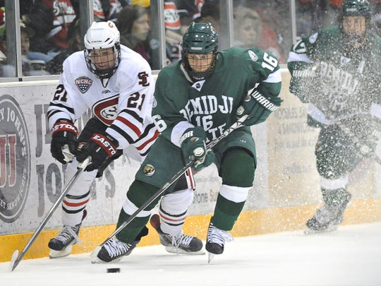 St. Cloud State's Brooks Bertsch (21) tries to get the puck from Bemidji State's Danny Mattson on Oct. 11, 2013, at the Herb Brooks National Hockey Center. Bertsch will begin his third season working for the Los Angeles Kings this fall, his first season as a scout.