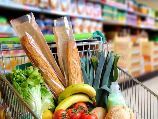 Shopping cart full of food in supermarket aisle elevated view