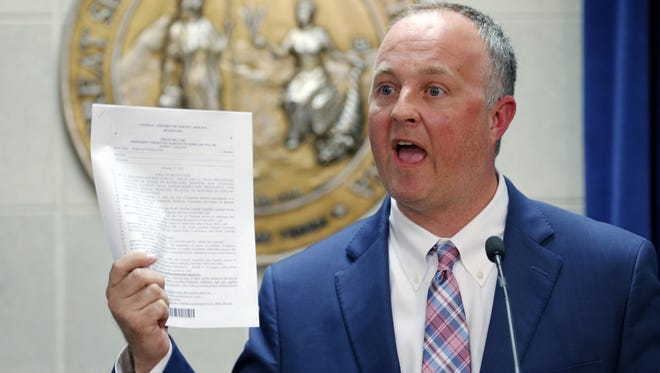 N.C. House Democratic leader Rep. Darren Jackson holds up a copy of HB 186, which was a compromise bill to replace HB2 that was introduced about a month ago, Tuesday, March 28, 2017, in Raleigh, N.C.