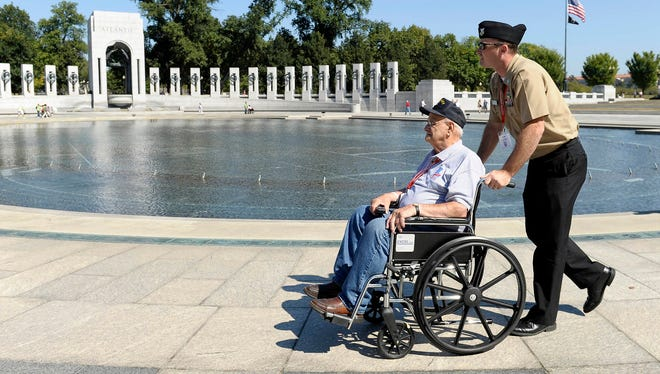 World War II veteran Gus Nicholas is pushed by U.S. Navy Petty Officer First Class Lee Hoffman as they visit the World War II Memorial on Oct. 2, 2013,  in Washington.