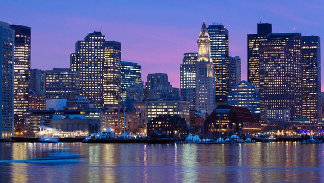 The Boston city skyline is illuminated at dusk as it reflects off the waters of Boston Harbor.