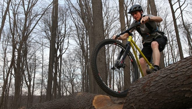 Tim Howland, from East Rochester, rides his bike on the trails at Tryon Park.