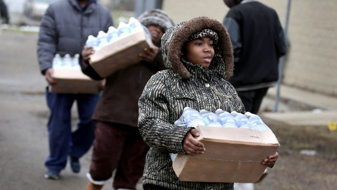 Flint residents pick up cases of bottled water at the Flint Fire Station 3 in Flint, MI on Tuesday, January 26, 2016.