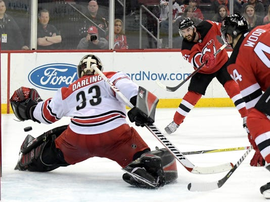 New Jersey Devils right wing Kyle Palmieri (21) scores a goal past Carolina Hurricanes goaltender Scott Darling (33) during the second period of an NHL hockey game Tuesday, March 27, 2018, in Newark, N.J. The Devils won 4-3.(AP Photo/Bill Kostroun)