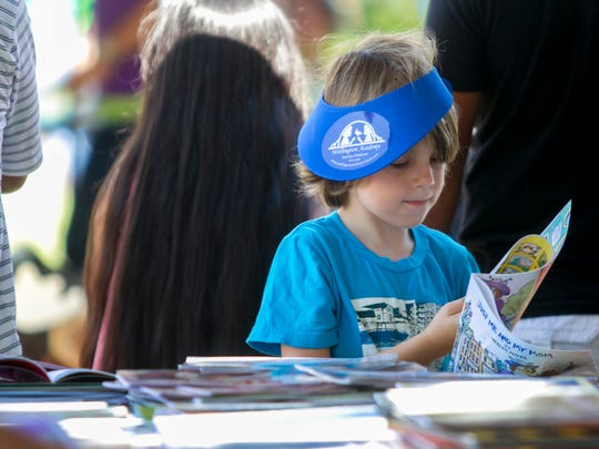 Riley Williams, 5, picks out a free book at the Southwest Florida Reading Festival on Saturday in downtown Fort Myers.