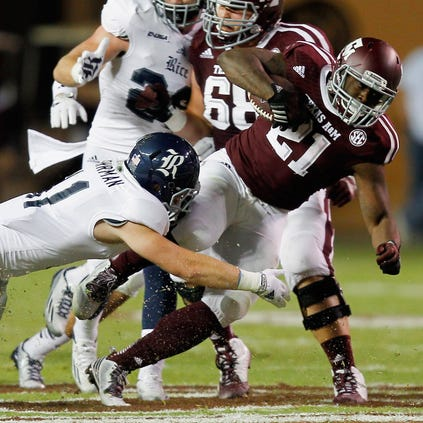 COLLEGE STATION, TX - SEPTEMBER 13:  Tra Carson #21 of the Texas A&M Aggies is tackled by Garrett Fuhrman #11 of the Rice Owls at Kyle Field on September 13, 2014 in College Station, Texas.  (Photo by Bob Levey/Getty Images)