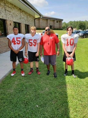 From left, Bryan County's Kameron Boggs (45), Marvin Brown (59), head coach Cherard Freeman and Sean Kelly Hill (10).