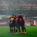 Barcelona's Lionel Messi (10) is congratulated by team mates after scoring against Sevilla during their Spanish First Division soccer match at Ramon Sanchez Pizjuan stadium in Seville, February 9, 2014. REUTERS/Marcelo del Pozo (SPAIN - Tags: SPORT SOCCER) ORG XMIT: MDP14