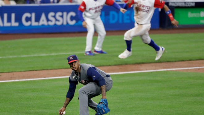 As U.S. pitcher Marcus Stroman, below, picks up the ball after a fielding error on a ball hit by Yadier Molina, Puerto Rico's Carlos Correa, back right, rounds third base during the third inning of a second-round World Baseball Classic baseball game Friday, March 17, 2017, in San Diego. Correa was tagged out and Molina reached second base on the play.