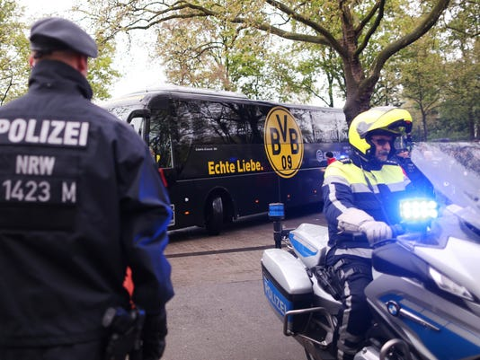 Police guard at the entrance of the Dortmund stadium prior to the German Bundesliga soccer match between Borussia Dortmund and Eintracht Frankfurt, in Dortmund, Saturday, April 15, 2017. Defender Marc Bartra and a police officer were wounded when three explosions hit the team bus as it was leaving for the stadium ahead of the first leg of the Champions League quarterfinal against Monaco Tuesday, April 11, 2017. . (Ina Fassbender/dpa via AP)