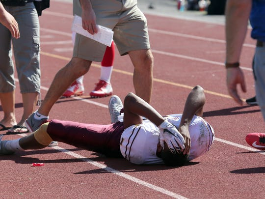 Arlington quarterback Justin Leigh holds his head after landing on the track, after being tackled at the edge of the football field during action in the home opener between North Rockland and Arlington at North Rockland High School, Sept. 5, 2015.