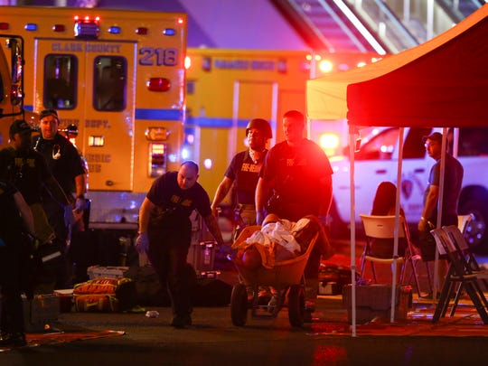 A wounded person is transported on a wheelbarrow as Las Vegas police respond during a shooting outside of Mandalay Bay on the Las Vegas Strip on Oct. 1, 2017. Multiple victims were being transported to hospitals after the gunfire at a country musical festival.