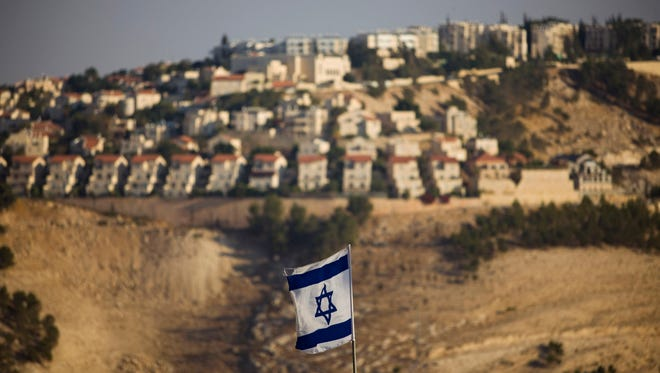FILE - In this Monday, Sept. 7, 2009 file photo, an Israeli flag is seen in front of the West Bank Jewish settlement of Maaleh Adumim on the outskirts of Jerusalem. The population of Jewish settlers in the occupied West Bank has surged during Prime Minister Benjamin Netanyahu's years in office, growing at more than twice the pace of the overall population, according to official figures obtained in December, 2014. (AP Photo/Bernat Armangue, File)