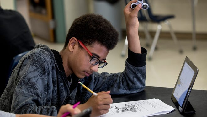 Willie Sanders, 13, uses a fidget spinner while working on an assignment during an eighth- grade science class Thursday, May 18, 2017 at Holland Woods Middle School in Port Huron.