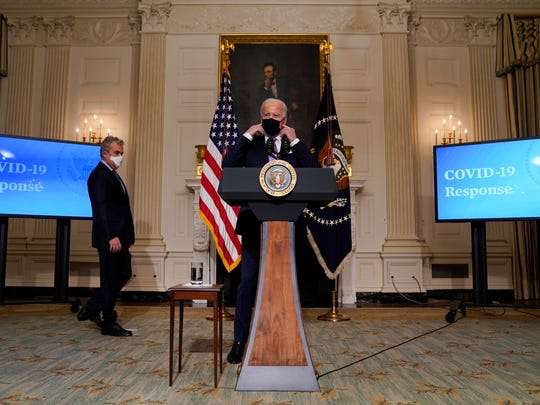 President Joe Biden removes his face mask before delivering remarks on COVID-19, in the State Dining Room of the White House on Tuesday.