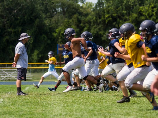 The Port Huron Northern Huskies run toward coach Larry Roelens at the end of a practice on Aug. 14. The Huskies' first game will be against Fraser at home at 7 p.m. Aug. 24.