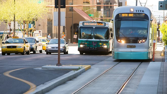 A Valley Metro bus and light rail train travel on Central Avenue near Van Buren Street in downtown Phoenix in Phoenix on Tuesday, March 10, 2015. Valley Metro and Glendale officials will present the latest information on a transit study of light-rail and bus-routes at a public meeting in Glendale on Sept. 17.