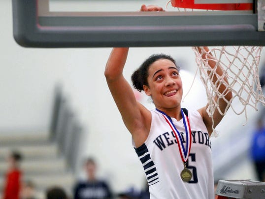 West York's Angie Hawkins cuts a piece of the net after the Bulldogs beat Delone Catholic, 47-35, to win the YAIAA girls' basketball championship.