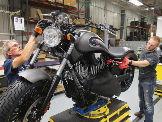 Arlan Reverts (L) and John Elliot put some finishing touches on a 2015 Victory Gunner motorcycle on the assembly line at the Polaris Industries factory on August 8, 2014 in Spirit Lake.